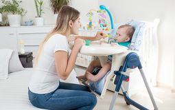 Young woman giving porridge on spoon to her baby sitting in highchair. Woman giving porridge on spoon to her baby sitting in highchair Royalty Free Stock Photography