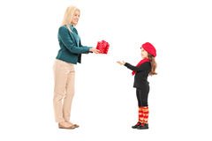 Young woman giving present to a little girl Stock Photos