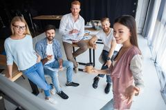 Group of young colleagues dressed casual standing together in modern office and brainstorming. royalty free stock photo