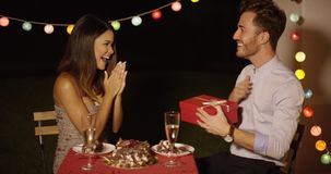 Young woman giving a surprise Valentines gift. To her boyfriend as they enjoy a romantic dinner together at a restaurant stock footage