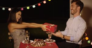 Young woman giving a surprise Valentines gift. To her boyfriend as they enjoy a romantic dinner together at a restaurant stock video