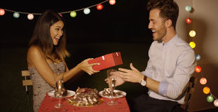 Young woman giving a surprise Valentines gift. Young women giving a surprise Valentines gift to her boyfriend as they enjoy a romantic dinner together at a Royalty Free Stock Image