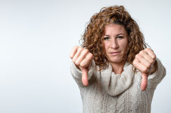 Young woman giving a thumbs down gesture. Attractive young woman giving a thumbs down gesture with both hands to register her disappointment and disapproval with Royalty Free Stock Image