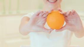 Young woman giving us fresh orange. Organic food stock footage