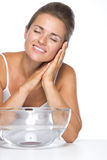 Young woman and glass bowl with water enjoying freshness Stock Photography