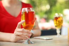 Young woman with glass of cold beer at table. Closeup stock photography