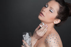 Young woman with glass of ice slices. royalty free stock photography