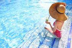 Young woman with glass of lemonade. In the pool stock image