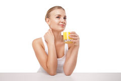 Young woman with a glass of orange juice isolated Stock Photos