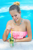 Young woman with a glass of refreshing lemonade in the pool Royalty Free Stock Image