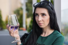 Young woman with a glass of violet cocktail on sits on the summer terrace of the restaurant royalty free stock photo