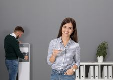 Young woman with glass of water near cooler. Young women with glass of water near cooler in office royalty free stock photo