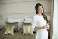 Young woman with glass of water in the room Stock Photography