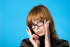 Young woman in glasses. Young and pretty woman looking over her glasses. Blue background royalty free stock image