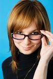 Young woman in glasses. Close-up portrait of young woman looking over her glasses stock image