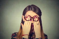 Young woman in glasses covering face eyes with hands Royalty Free Stock Images