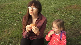 A young woman in glasses with a cute little girl eating one hamburger together stock footage