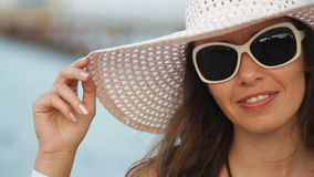 Young woman in glasses and a hat on a beach near the sea.  stock footage