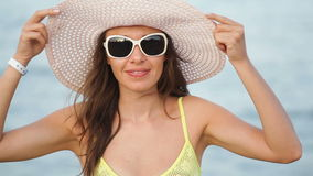 Young woman in glasses and a hat on a beach near the sea.  stock video