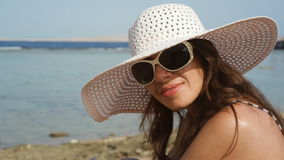 Young woman in glasses and a hat on a beach near the sea.  stock video footage