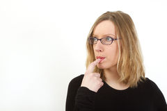 Young woman with glasses have finger in her mouth Royalty Free Stock Photography