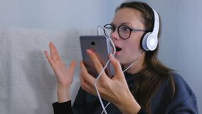 Young woman in glasses and headphones is listening a music on smartphone and singing a song in karaoke. Young woman in glasses and headphones is listening a stock video