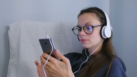 Young woman in glasses and headphones is listening a music on smartphone. Young woman in glasses and headphones is listening a music on smartphone stock video