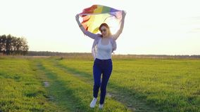 Young woman holding an LGBT flag runs across a field at sunset slow mo. Young woman in glasses holding an LGBT flag runs across a field at sunset slow mo stock video footage
