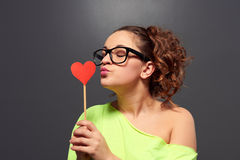 Young woman in glasses kissing paper heart Royalty Free Stock Photography