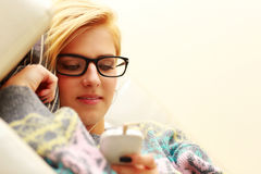 Young woman in glasses listening music Stock Photo
