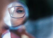 Young woman in glasses looking in cosmetic mirror, close up royalty free stock image