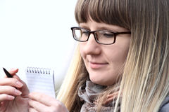 Young woman in glasses making notes using small notebook Royalty Free Stock Photo