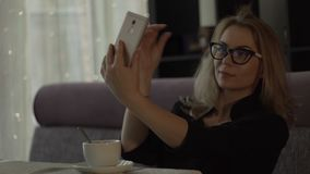 Young woman in glasses making selfie on mobile phone during lunch in trendy cafe. Young woman in glasses making selfie on mobile phone on background interior stock footage