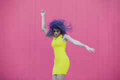 Young woman with glasses and purple afro hair dancing on a pink w Stock Photos
