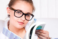 Young woman in glasses reading Royalty Free Stock Image