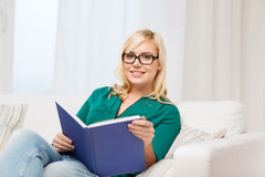 Young woman in glasses reading book at home Royalty Free Stock Photo
