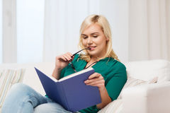 Young woman with glasses reading book at home Stock Photo