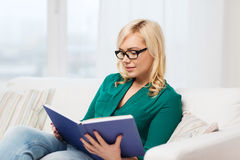Young woman in glasses reading book at home Stock Image