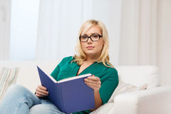Young woman in glasses reading book at home Royalty Free Stock Photography