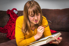 Young woman with glasses reading a book Stock Photos