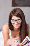 Young woman with glasses reading magazine at home Stock Images