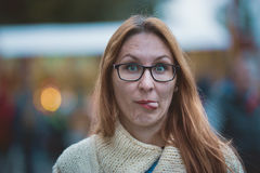 Young woman with glasses and red lips shows tongue, outdoor Royalty Free Stock Images