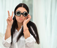 Young woman in glasses showing victory sign standing Stock Photos