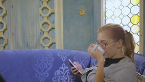 Young woman in glasses sitting in an Asian cafe drinking tea and using the Internet in a smartphone. Young woman in glasses sitting on a sofa in an Asian cafe stock video footage