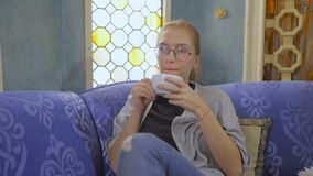 Young woman in glasses sitting in an Asian cafe drinking tea and using the Internet in a smartphone. Young woman in glasses sitting on a sofa in an Asian cafe stock video