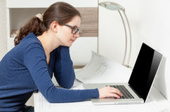 Young woman in glasses sitting behind table and looking at laptop Royalty Free Stock Photos