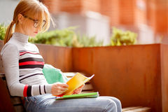 Young woman in glasses sitting on bench Royalty Free Stock Image