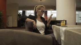 Young woman in glasses sitting in luxurious armchair and using mobile phone. On background interior cafe. Beautiful woman typing message on smartphone during stock footage