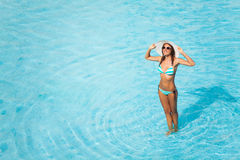 Young woman with glasses stands in blue water Stock Photography