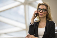 Young  woman with glasses talking on mobile phone in the business center. Stock Images